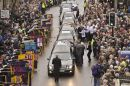 People place flowers on top of the hearse's as six fallen soldiers pass through the Wiltshire town
