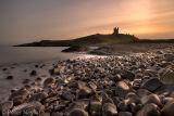 Dunstanburgh Rocks under Orange Sky